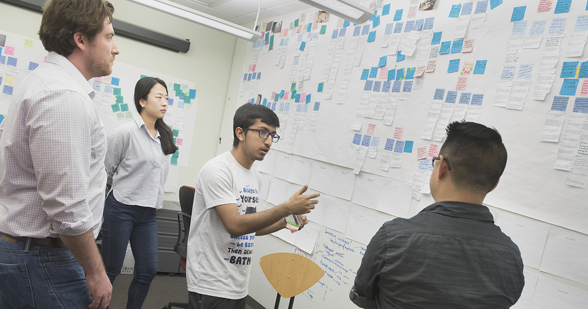 Students applying sticky notes to white board