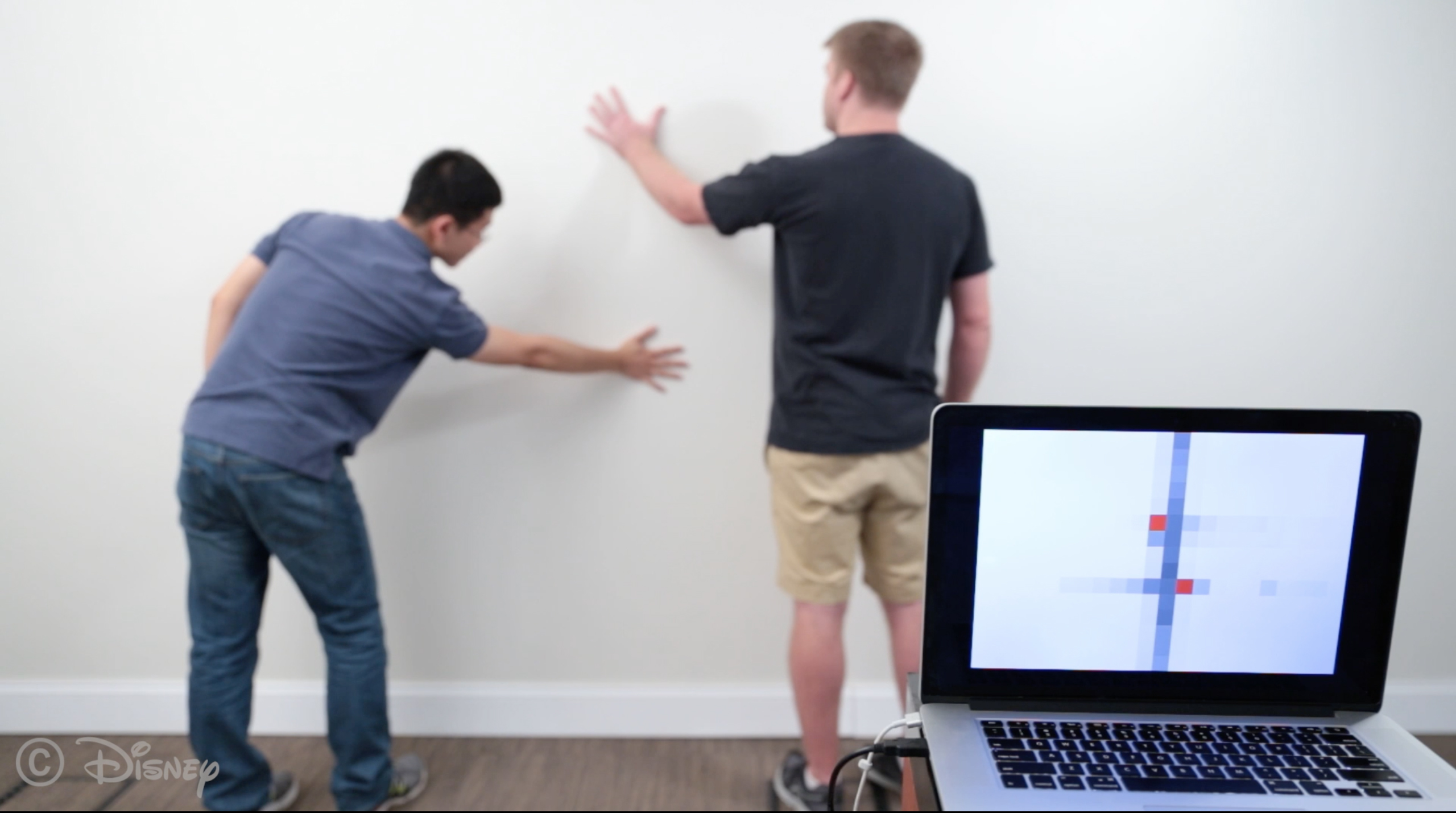 a person touches a wall in 2 places which is recognized by the wall's sensors and displayed on a nearby laptop screen
