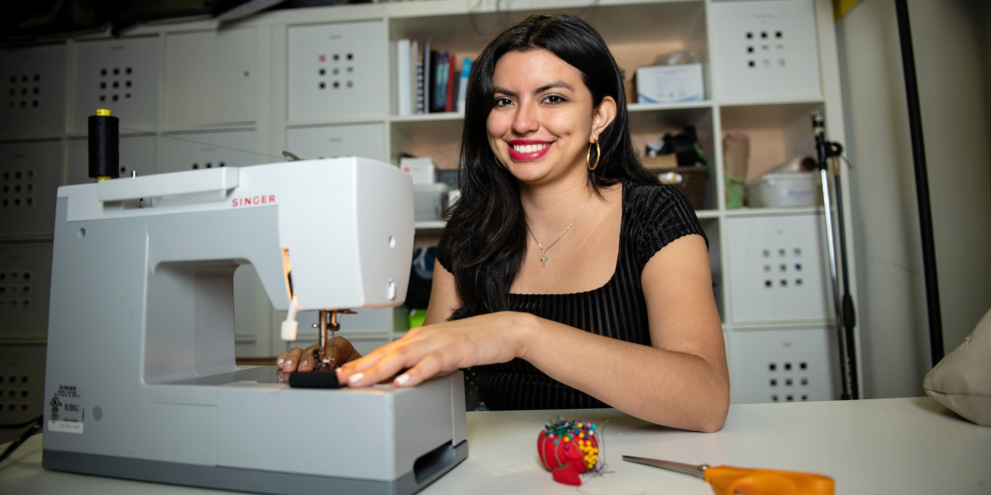 Ashley Burbano uses a sewing machine in the lab