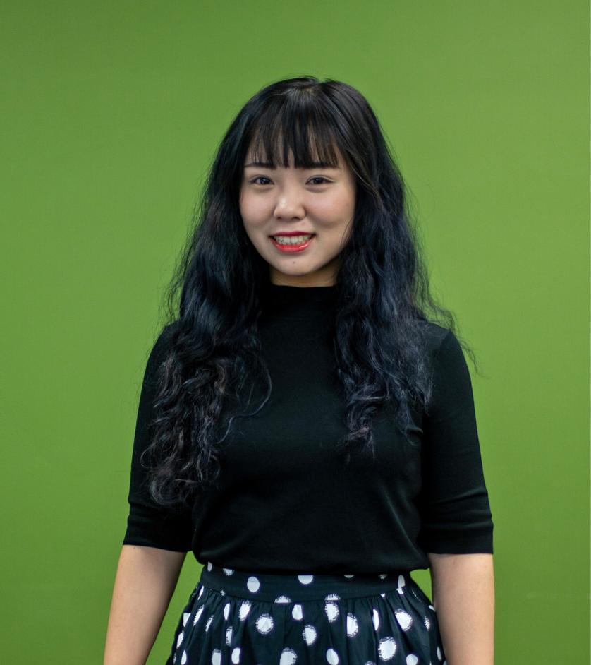 Alice Li stands in front of MHCI green wall