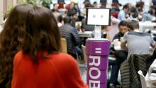 a robot with a purple torso is in the forground of a crowded cafeteria