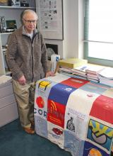 Dan Siewiorek stands beside the t-shirt quilt in his office