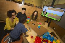 3 adults and a child sit at the NoRILLA table and build towers with blocks