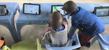 the view of the back two young boys interacting with a touchscreen tablet sitting on a plastic table