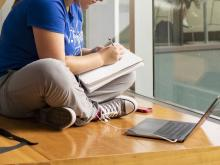 student seated with legs crossed on the floor writing in notebook and laptop open on floor nearby