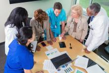 6 doctors and nurses stand around the end of a table looking at charts, graphs and a laptop