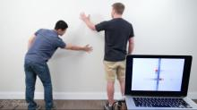 Two men stand in front of a white wall. The locations of where they are touching the wall are visible on a nearby laptop screen.