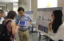 4 students in foreground at a research fair. One student holds laptop open while another student completes a demo. A line of posters on easel down the hall is visible in background